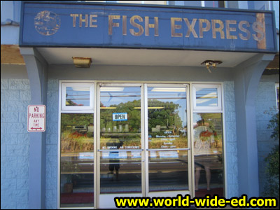 Sign outside The Fish Express (and some goon's reflection)