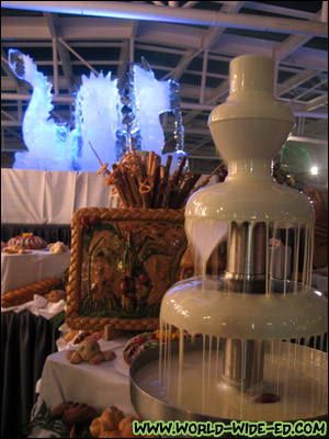 White chocolate fountain with a dragon ice sculpture in the background at the Dessert Extravaganza