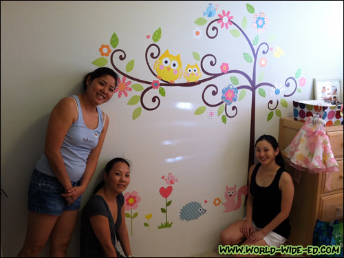 Noele and Shorty help wifey put the decals on baby's bedroom wall