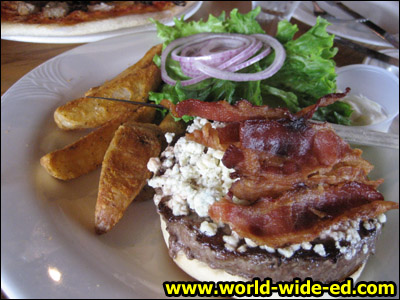 Bacon - Blue Cheeseburger - Smoked bacon and blue cheese cover this 1/2 lb. Black Angus burger charbroiled to perfection and topped with onions, tomatoes and lettuce on a toasted sesame bun. - $13