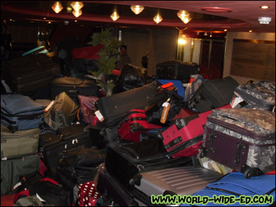 Mystery solved: the pile of luggage (ours is in there somewhere) [Photo Credit: Lee Kojima]