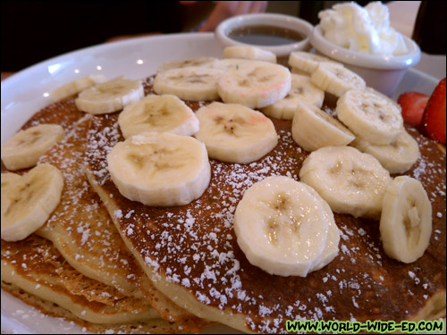Buttermilk Pancakes with Bananas - 3 light and fluffy pancakes dusted with powdered sugar, served with butter and syrup. Served with bananas, blueberries, caramelized apples or strawberries $1.50 each. ($6.95 + $1.50)