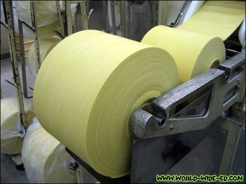 Large flour rolls feeding into the machine that cuts them into noodles